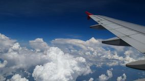 4K footage airplane flight. wing of an airplane flying above the white clouds and blue sky. beautiful aerial view from the window. Of the plane on travelling stock video