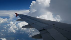 4K footage airplane landing flight. wing of an airplane flying in to the white clouds and blue sky. stock footage