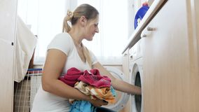 4k video of beautiful young housewife loading and turning on washing machine. 4k footage of beautiful young housewife loading and turning on washing machine stock video footage
