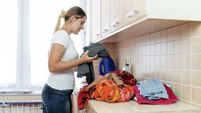 4k video of beautiful young woman sorting piles of dirty clothes at laundry