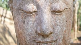 4K footage. Calm and peaceful face of old worship buddha statue head illuminated. Buddha statue at Chiangmai history temple. Chian. G Mai Province, Thailand stock video footage