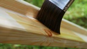 4K footage. Close-up paintbrush varnishing wooden plank.  stock footage