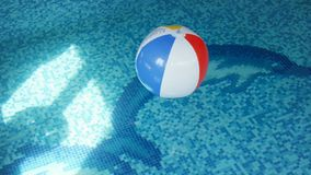 4k footage of colorful striped beach ball swimming in pool. Inflatable ball on water surface stock video footage