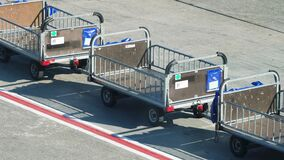 4k video of empty trolleys or carts for delivering and loading luggage and bags in passenger airplane in airport