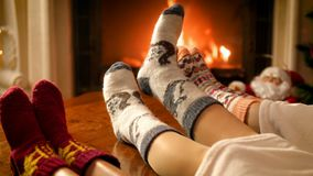 Closeup 4k footage of family feet lying on sofa under blanket warming at burning fireplace stock video footage
