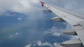 4K footage. flight over the rainbow. aerial view through an airplane window. wing airplane and beautiful white clouds in blue sky. For travel background stock video
