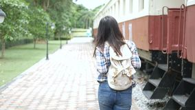 4K footage. happy Asian tourist woman at railway station, walk to the train and step up on stair. travel in Asia by vintage train. stock footage