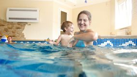 4k video of happy smiling young mother with 3 years old toddler boy swimming and playing in pool at gym stock video