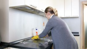 4k video of housewife in rubber gloves spraying detergent over electric hob and washing it with sponge. 4k footage of housewife in rubber gloves spraying stock footage