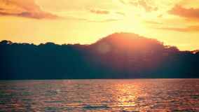 Establishing shot of an island at sunset. 4K footage of an island as the sun sets behind it stock footage