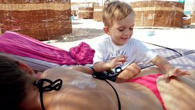 4k video of little toddler boy applying sunscreen creme on young mother lying on the sunbed at sea beach
