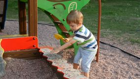 4k video of little toddler boy playing in sandbox and throving sand with gravel. 4k footage of little toddler boy playing in sandbox and throving sand with stock video