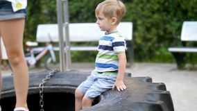 4k footage of little todler boy sitting on big tiry on children playground at park stock video footage