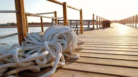 4k footage of long wooden pier at sunset rays. WHite ropes and cables lying on the wooden deck. 4k video of long wooden pier at sunset rays. WHite ropes and stock video footage