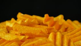 4K footage of pile of fluted potato chips with spices like paprika or chili pepper, rotating over black background, medium speed. 4K UHD footage of pile of stock video