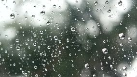 4K footage. rain running up on clear window glass surface with green tree and bokeh light outside at background. rain drop stock footage
