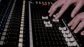 4K footage of a recording studios audio console and a hand pulling up the knobs The audio console royalty free stock image
