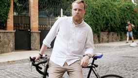 4k footage of stylish bearded man in white shirt leaning on bicycle on old street. 4k video of stylish bearded man in white shirt leaning on bicycle on old stock video footage