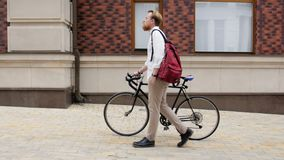 4k video of stylish hipster man with red beard walking on old street with vintage black bicycle. 4k footage of stylish hipster man with red beard walking on old stock footage