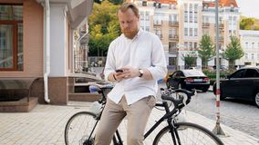 4k video of stylish hipster man sitting on bicycle and typing message on cell phone. 4k footage of stylish hipster man sitting on bicycle and typing message on stock video