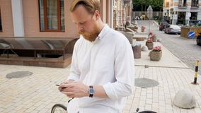4k footage of stylish red bearded man in white shirt sitting on vintage bicycle and typing message on his mobile phone. 4k video of stylish red bearded man in stock video footage