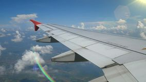 4K footage. traveling by air. aerial view through an airplane window with light from len flare. Wing airplane and beautiful white clouds in blue sky for stock footage