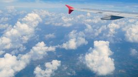4K footage. traveling by air. aerial view through an airplane window. wing airplane and beautiful white clouds in blue sky stock footage
