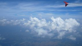 4K footage. Traveling by air. Aerial view through an airplane window. Wing airplane and beautiful white clouds in blue sky. For background stock footage