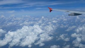 4K footage. traveling by air. aerial view through an airplane window. wing airplane and beautiful white clouds in blue sky. For background stock video footage