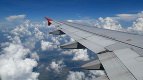 4K footage. traveling by air. aerial view through an airplane window. wing airplane and beautiful white clouds in blue sky. For travel background stock video