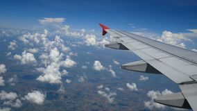 4K footage. traveling by air. aerial view through an airplane window. wing airplane and beautiful white clouds in blue sky. For travel background stock footage