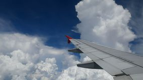 4K footage. traveling by air. aerial view through an airplane window. wing airplane between turn direction for landing time. And beautiful white clouds in blue stock footage