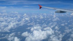 4K footage. traveling by air. aerial view through an airplane window. wing airplane and beautiful white clouds in blue sky. For background stock video
