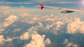 4K footage. traveling by air. aerial view through an airplane window. wing airplane at sunset or sunrise time with lens flare. And beautiful white clouds in stock video footage