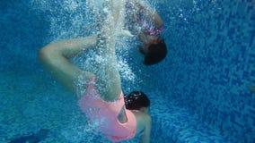 4k video of two teenage girls diving underwater at indoor swimming pool. Children having fun and enjoying water. 4k footage of two teenage girls diving stock video