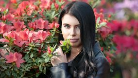 4K footage of young attractive woman in black leather jacket posing over green exotic background with flowers. 4K footage of young attractive woman in black stock footage