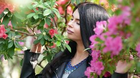 4K footage of young attractive woman posing over green exotic background with big leaves and flowers. In orangery or greenhouse stock video