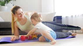 4k footage of young mother exercising on fitness mat at home with her cute baby boy playing on floor stock video