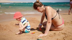 4k video of young mother with her child son playing with toy car on the sea beach. Family relaxing during summer beach stock video footage