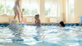 4k video of young mother, two teenage girls and toddler boy having fun in indoor swimming pool. 4k footage of young mother, two teenage girls and toddler boy stock video