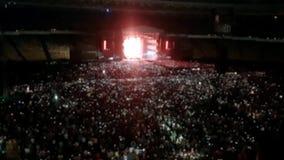 4k fora do vídeo do foco de luzes coloridas brilhantes na cena do concerto de rocha Multidão de povos que escutam a música em esp video estoque