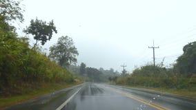 4K fronteggiano la vista dell'automobile che passa la strada unsmooth della campagna con goccia di pioggia e la scossa