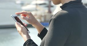4k A girl using a smartphone at seaside,yacht & sailing in the harbour. Gh2_11094_4k stock footage