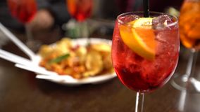 4K, Glasses of sparkling wine with aperol cocktail and appetizer platter. With chips fried potatoes and pasta on the table at restaurant. Italian aperitives at stock footage