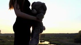 4k - Gravid flickalek för barn med björnen på solnedgången stock video