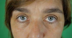 4K - Grijs-blauwe ogen van een volwassen vrouw, een verraste blik dicht omhoog, chromakey stock video
