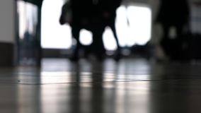 Soft focus people walking through an airport terminal with suitcases, bags and baggage. 4K ground level soft focus video clip of anonymous people walking through stock video footage