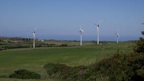 4K wind turbines in traditional farmland blue sky UK stock video footage