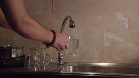 4K häller vatten från klappet in i ett klart exponeringsglas stock video