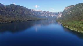4K Hög flyg och start ovanför att förbluffa Bohinj sjön i morgonen Blåa djupt vatten och Julian Alps berg Triglav NP arkivfilmer
